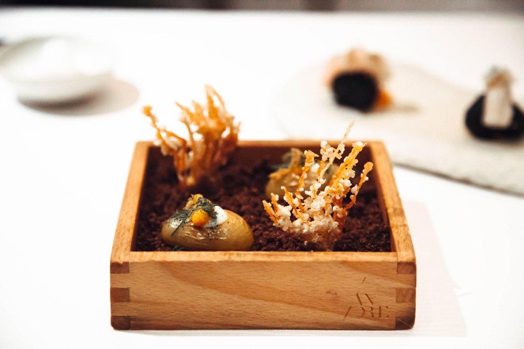 Patatas bravas and fried prawn head in chocolate-garlic soil